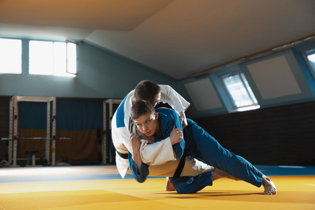 Two young judo fighters in kimono training martial arts in the gym with expression, in action and